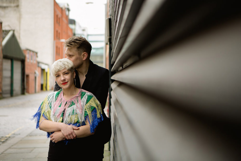 cool and creative manchester portrait photo of couple against textured wall