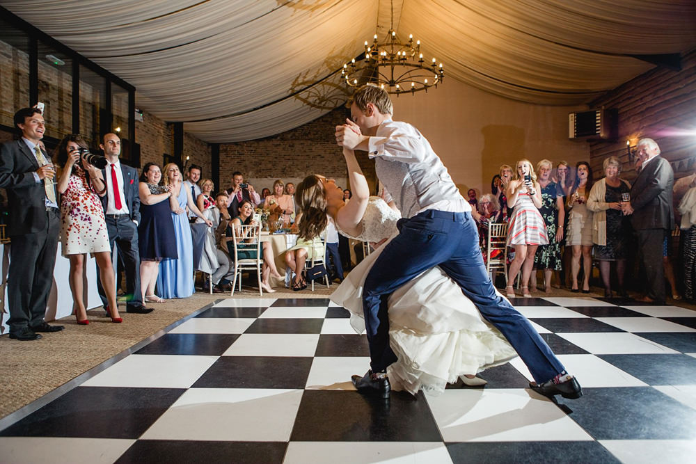 Photo of fun and lively first dance in wedding barn
