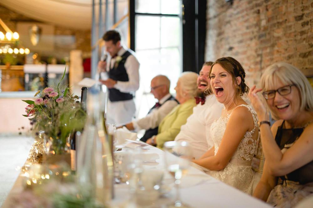 bride laughing during speeches in hornington manor wedding barn