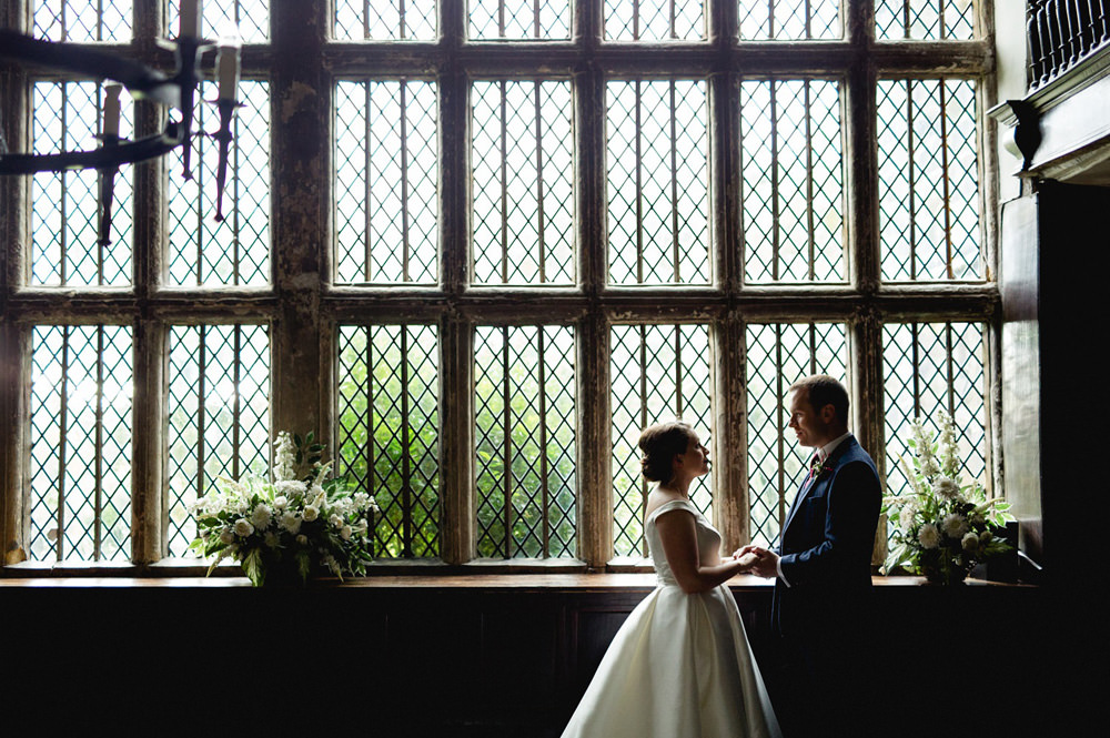 Creative Portrait of wedding couple in front of Oakwell Hall Windows