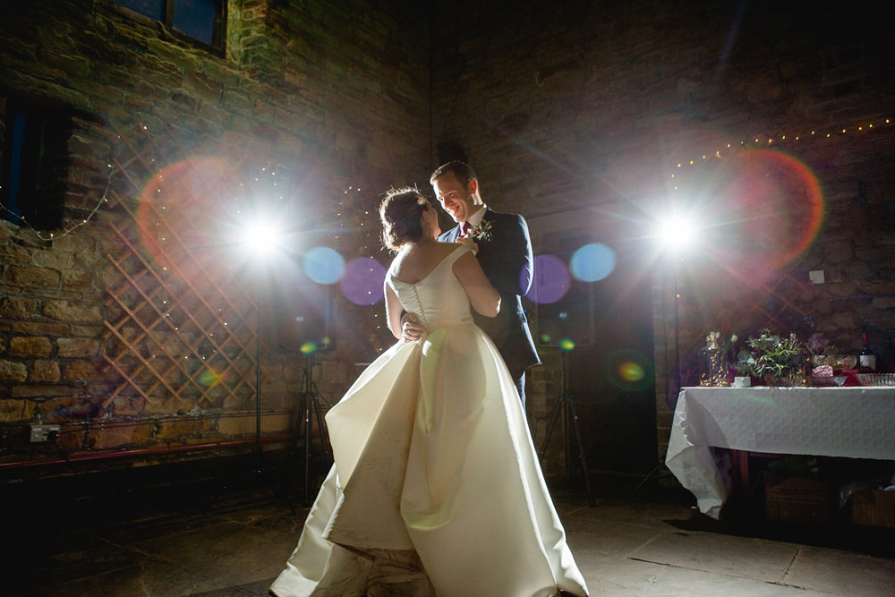 dramatic first dance photo in barn wedding venue
