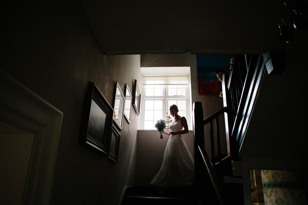 Creative portrait of bride walking down stairs at Talton lodge