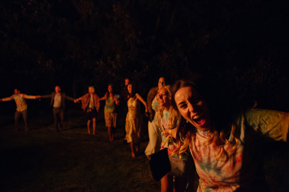 fun photo of wedding guests dancing around a bonfire at talton lodge