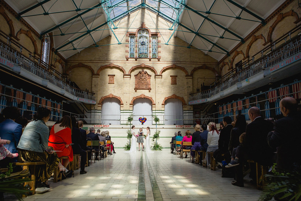 Natural light during ceremony at The Turkish Baths stained glass window at Victoria Baths Wedding Venue Manchester