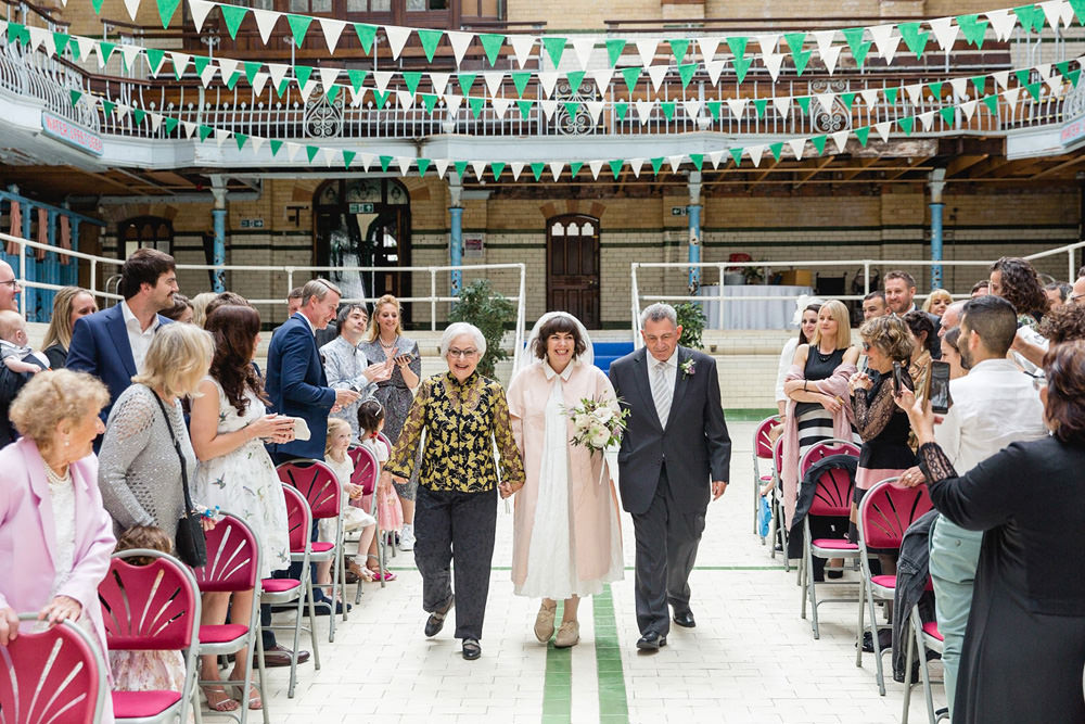 bride and parents walking down the aisle at Victoria baths wedding venue manchester