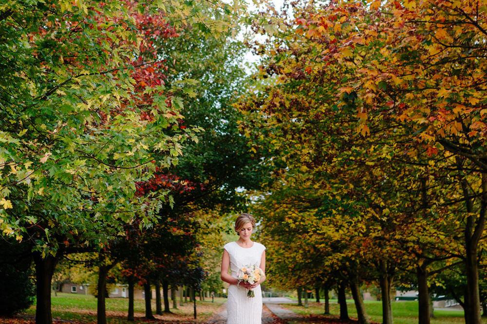 Portrait of bride at Yorkshire sculpture park wedding venue against autumn trees