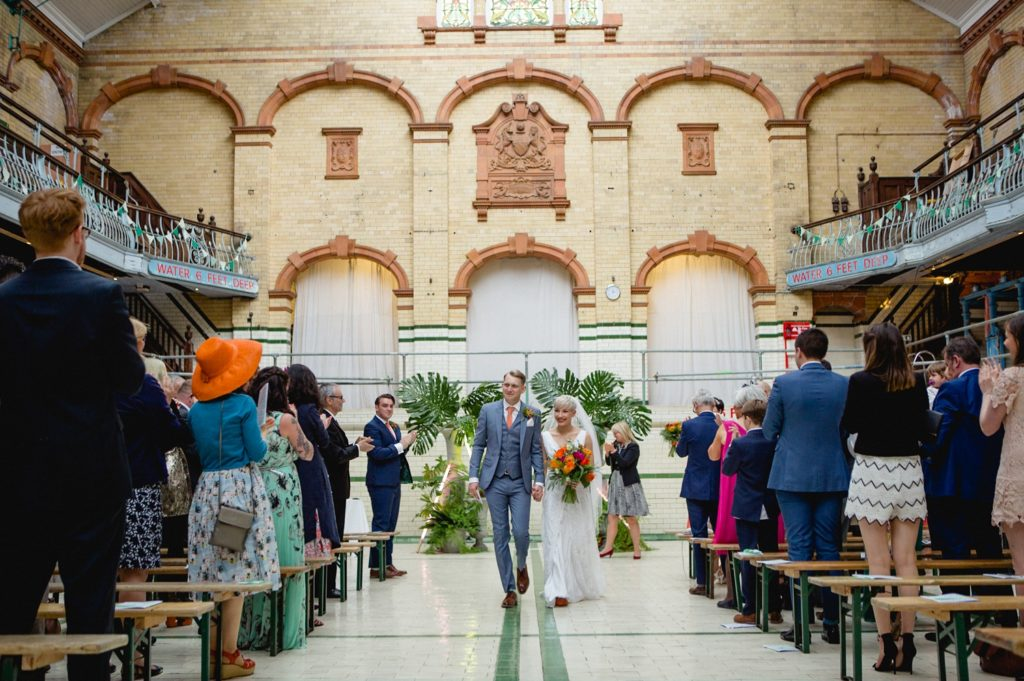 Couple walking down the aisle after wedding ceremony at Victoria Baths Manchester