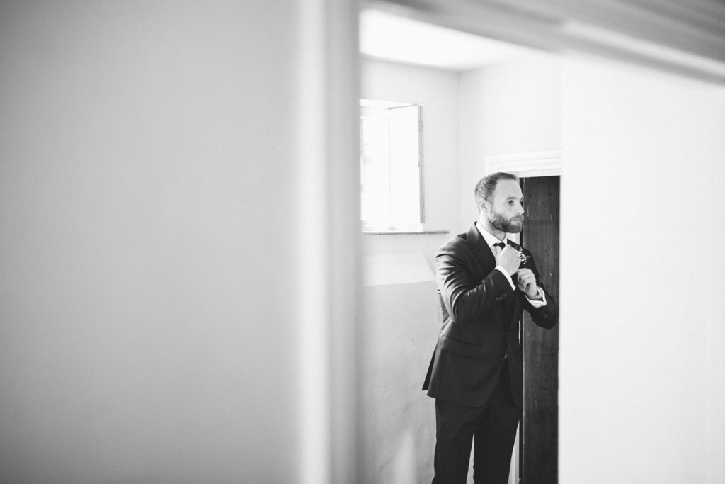 creative photo of groom getting ready in front of mirror