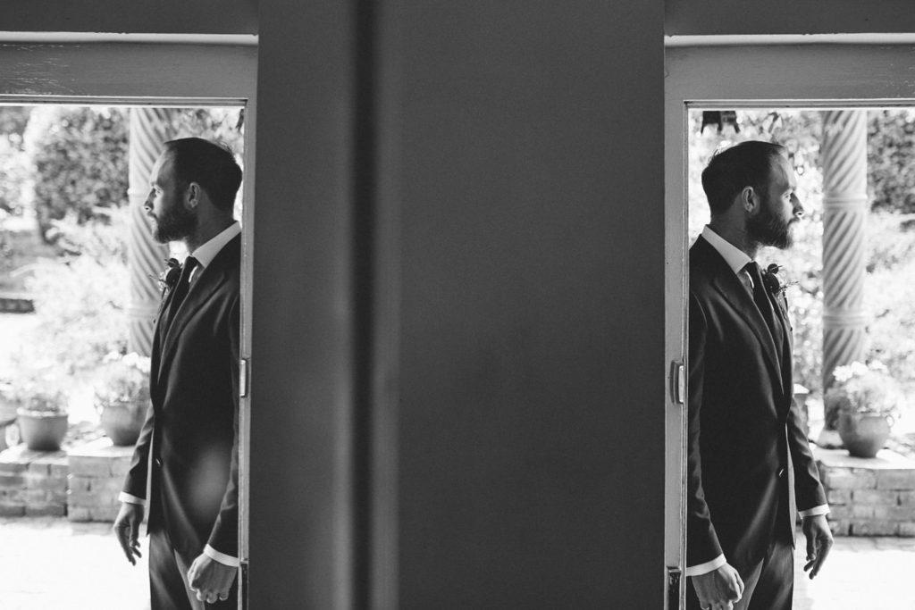 alternative wedding photo of groom in doorway
