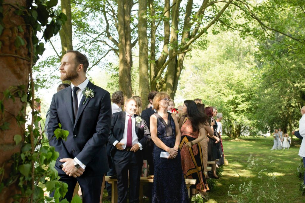 groom waiting for bride at top of aisle before their outdoor garden wedding kent