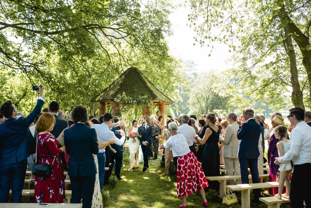 walking down the aisle as guests throw confetti on outdoor garden wedding