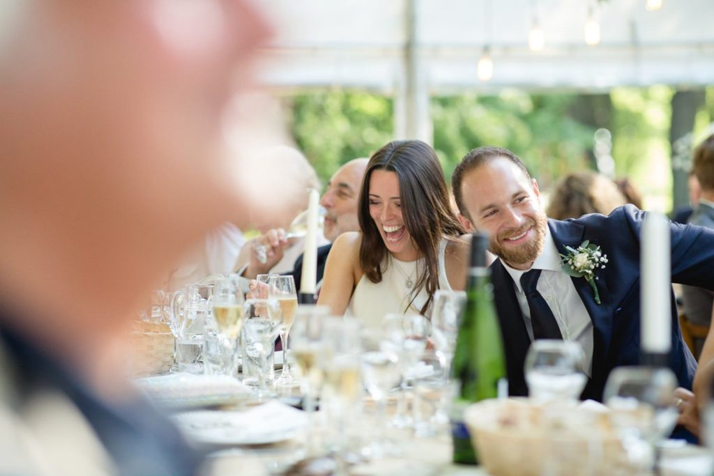 natural photo of bride and groom laughing during wedding speeches