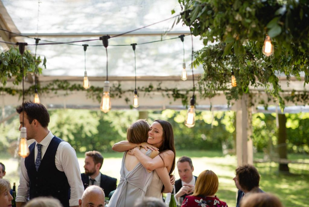 documentary photo of bride hugging sister at her modern outdoor garden wedding