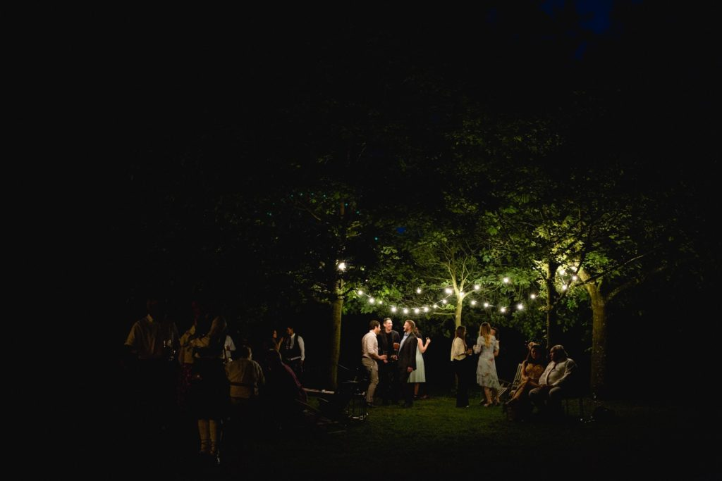 nighttime wedding photo of guests under trees and lighting