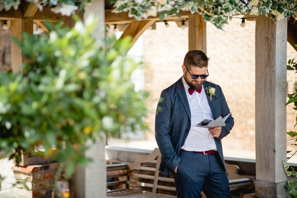natural photo of groom reading card before his wedding outside at hornington manor york