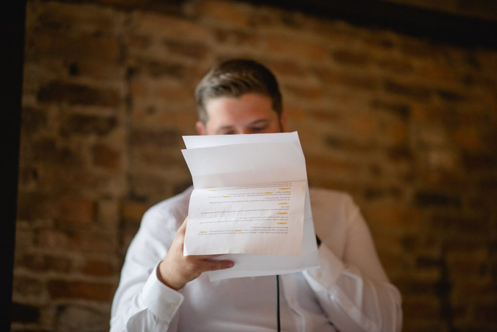 creative wedding photo of groom reading speech